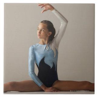 Female gymnast (12-13) performing splits tile
