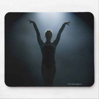 Female gymnast performing in spotlight, studio mouse mat
