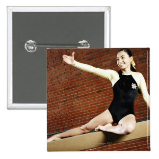 Female gymnast practicing on a balance beam and 15 cm square badge