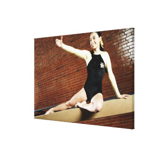 Female gymnast practicing on a balance beam and canvas print