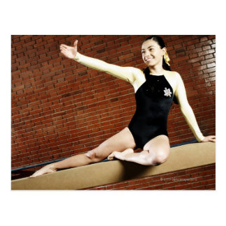 Female gymnast practicing on a balance beam and postcard