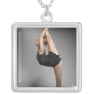 Female gymnast stretching, studio shot silver plated necklace