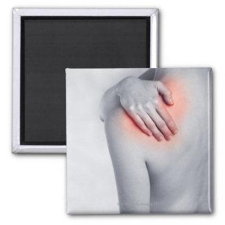 Female hands holding the shoulder and massaging square magnet
