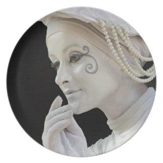 Female mime performing on street corner plate
