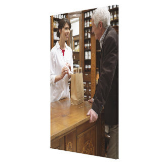 Female pharmacist advising customers canvas print