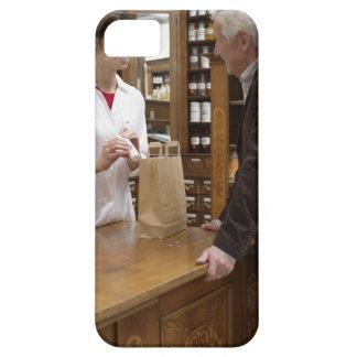 Female pharmacist advising customers iPhone 5 cases
