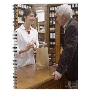 Female pharmacist advising customers notebooks