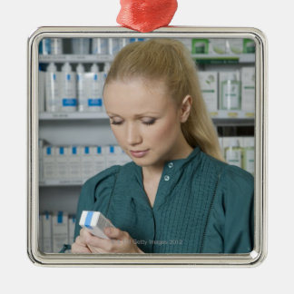Female pharmacist looking at medicine in 2 christmas ornament