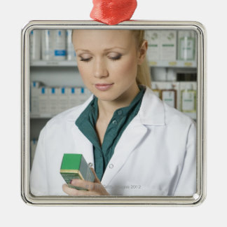 Female pharmacist looking at medicine in christmas ornament