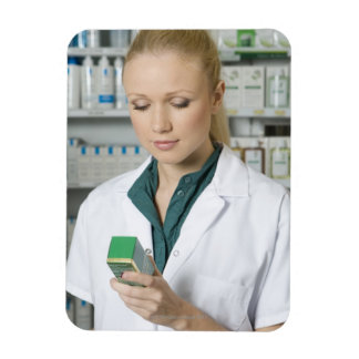 Female pharmacist looking at medicine in magnet