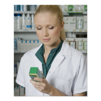 Female pharmacist looking at medicine in poster