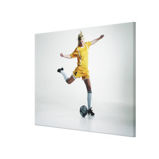 Female soccer player preparing to kick soccer canvas print