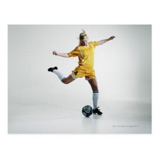 Female soccer player preparing to kick soccer postcard