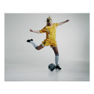 Female soccer player preparing to kick soccer poster