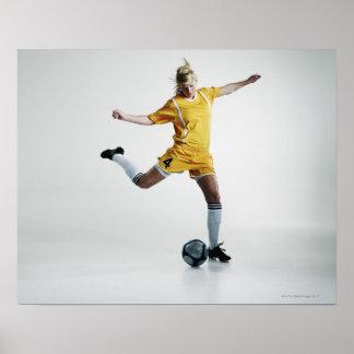 Female soccer player preparing to kick soccer poster