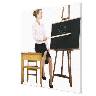 Female Teacher Pointing Ruler at Chalkboard Canvas Print
