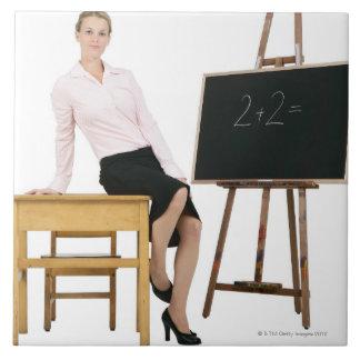 Female Teacher Posing by Wooden Desk Large Square Tile