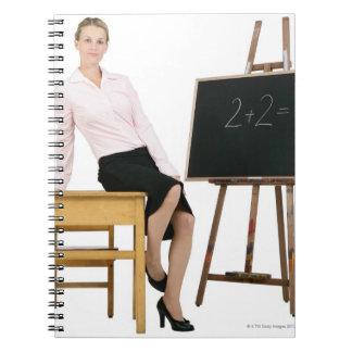 Female Teacher Posing by Wooden Desk Notebooks