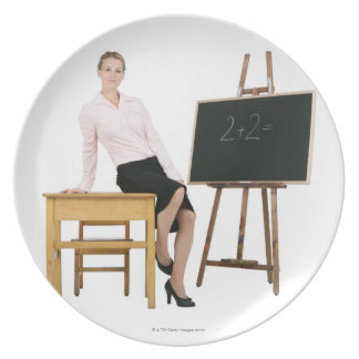 Female Teacher Posing by Wooden Desk Plate