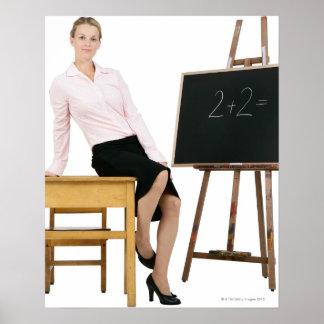 Female Teacher Posing by Wooden Desk Poster