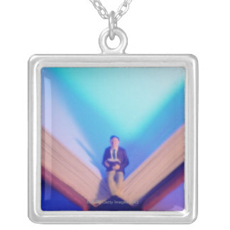 Figurine sitting on open book necklace