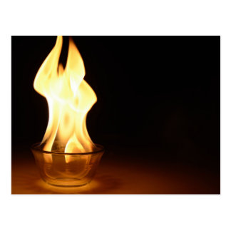 Fire in a bowl isolated in black. postcard