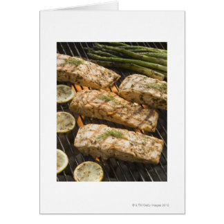 Fish and asparagus cooking on grill card