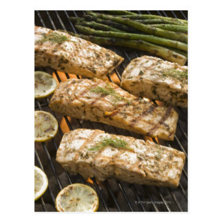 Fish and asparagus cooking on grill postcard