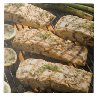 Fish and asparagus cooking on grill tiles