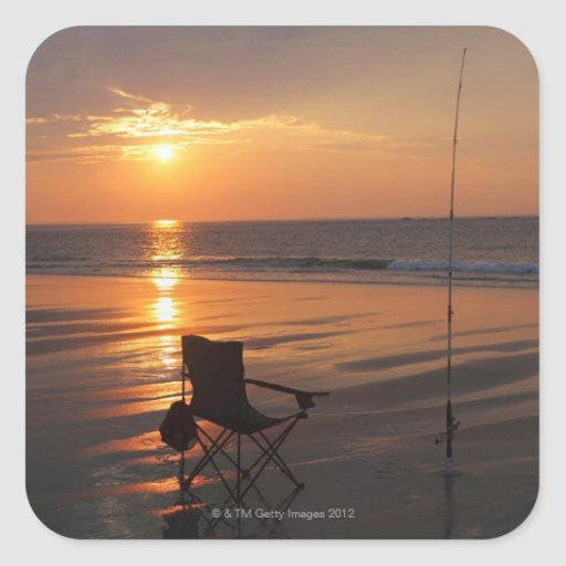 Fishing rod and chair by the ocean in the early square sticker