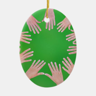 Five children hands joining in circle above green christmas ornament