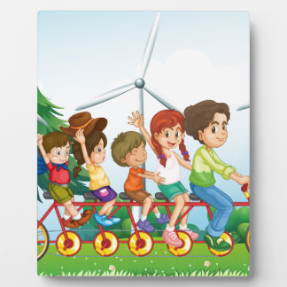 Five kids riding at the bike near the windmills plaque