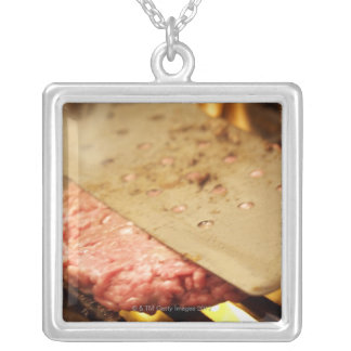 Flattening a Hamburger Patty with a Spatula on Silver Plated Necklace