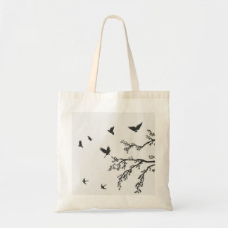 flock of flying birds on tree branch tote bag