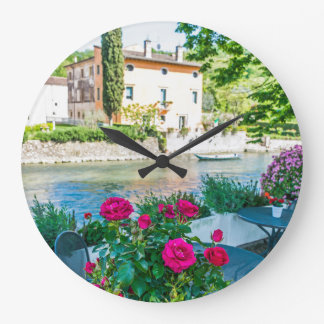 Flowers by the river wall clock