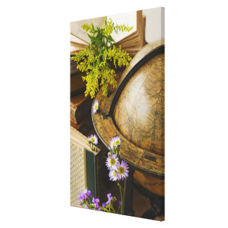 Flowers with antique globe and books canvas print