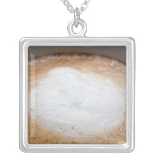 Foam on cappuccino, close-up silver plated necklace