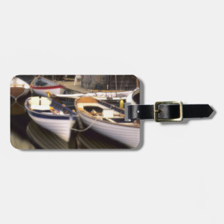 Fog surrounds four boats docked. luggage tag