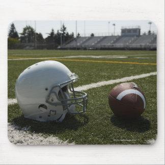 Football and football helmet on football field mouse mat