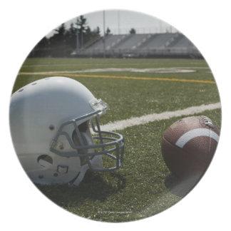 Football and football helmet on football field plate