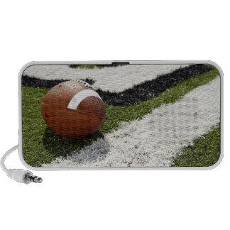 Football at goal line on football field, laptop speaker