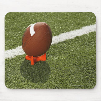 Football atop tee on football field, elevated mouse mat
