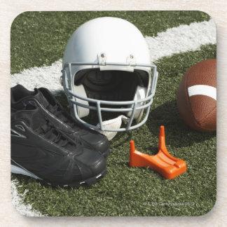 Football, football helmet, tee and shoes on coaster
