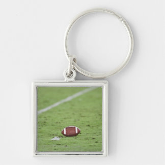 Football near yardage line. Silver-Colored square key ring
