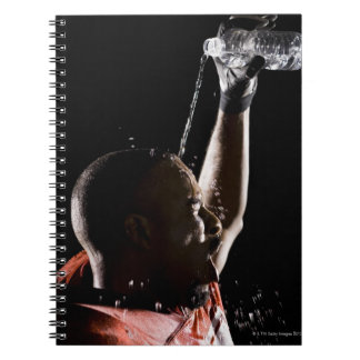 Football player cooling off with water notebooks