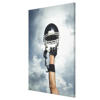 Football player holding helmet in air canvas print