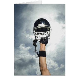 Football player holding helmet in air greeting card