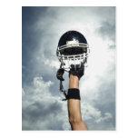 Football player holding helmet in air postcard