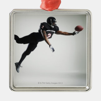 Football player leaping in mid air to catch ball christmas ornament