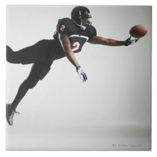 Football player leaping in mid air to catch ball large square tile